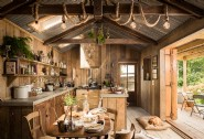 Rustic open-plan kitchen with double barn doors opening onto the front deck